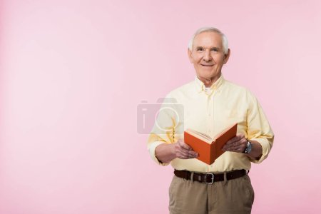 Photo for Positive retired man holding book and smiling on pink - Royalty Free Image