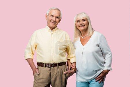 Photo pour Homme retraité heureux avec la main dans les mains de fixation de poche avec la femme gaie d'isolement sur le rose - image libre de droit