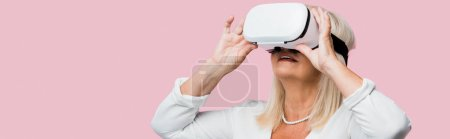 Photo for Panoramic shot of retired woman touching virtual reality headset isolated on pink - Royalty Free Image