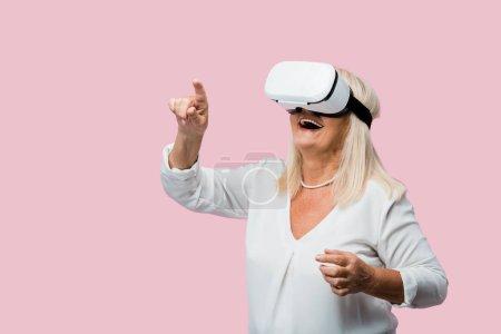 Photo pour Femme retraité pointant avec le doigt tout en portant le casque de réalité virtuelle isolé sur le rose - image libre de droit