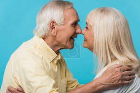 Foto de Hombre jubilado feliz mirando a la esposa alegre y sonriendo aislado en azul - Imagen libre de derechos