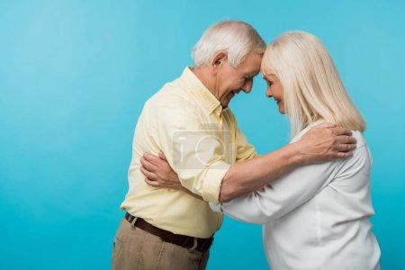 Foto de Vista lateral de la pareja jubilada alegre con los ojos cerrados sonriendo aislado en azul - Imagen libre de derechos