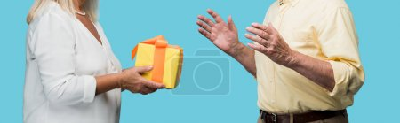 panoramic shot of retired woman giving yellow gift box to senior husband isolated on blue