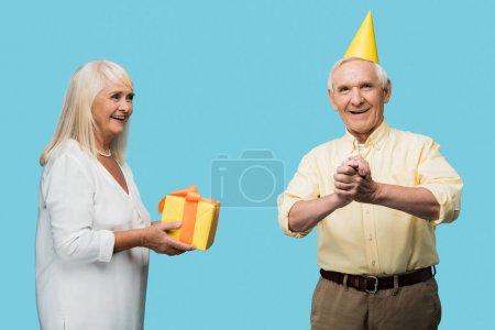 Photo pour Femme à la retraite donnant boîte cadeau jaune au mari aîné heureux isolé sur bleu - image libre de droit