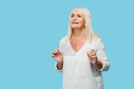Photo pour Femme aînée émotive avec les gesticulants gris de cheveux isolés sur le bleu - image libre de droit