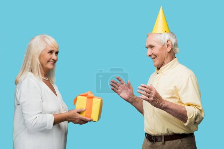 happy retired woman giving yellow gift box to senior husband isolated on blue
