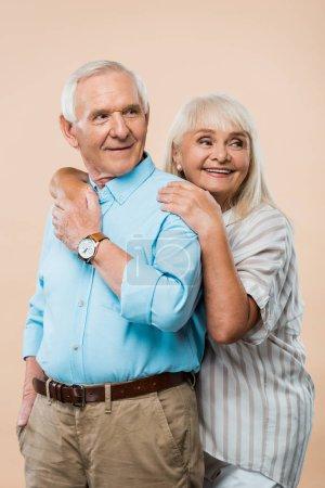 Photo pour Femme retraitée gaie étreignant le mari tout en retenant des mains d'isolement sur le beige - image libre de droit