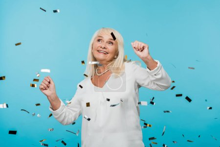 Photo for Happy retired woman looking at falling confetti on blue - Royalty Free Image
