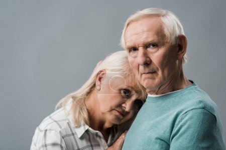 Photo for Upset retired man standing with frustrated wife isolated on grey - Royalty Free Image