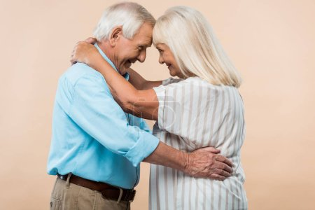 cheerful retired couple looking at each other while hugging isolated on beige