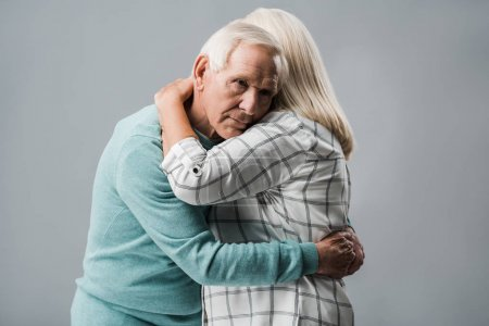 Photo for Sad retired man hugging senior wife and looking at camera isolated on grey - Royalty Free Image