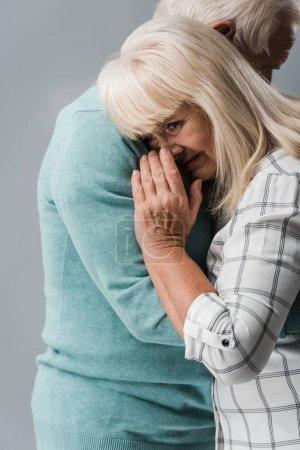 Photo pour Vue recadrée de mari étreignant la femme retraitée couvrant le visage tout en pleurant isolé sur le gris - image libre de droit