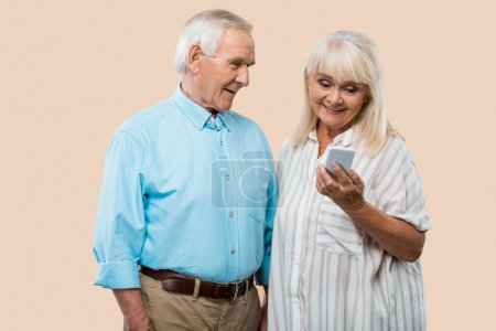 Photo for Cheerful retired man looking at wife holding smartphone isolated on beige - Royalty Free Image
