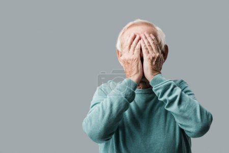 Photo for Senior man with grey hair covering face with hands isolated on grey - Royalty Free Image