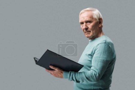 Photo pour Bouleversé retraité avec les cheveux gris tenant album photo isolé sur gris - image libre de droit
