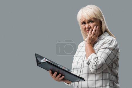 Photo pour Femme retraitée bouleversée retenant l'album de photo et touchant le visage isolé sur le gris - image libre de droit
