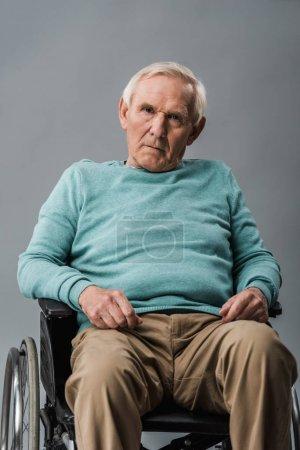 Photo pour Homme aîné bouleversé s'asseyant dans le fauteuil roulant et regardant la caméra d'isolement sur le gris - image libre de droit