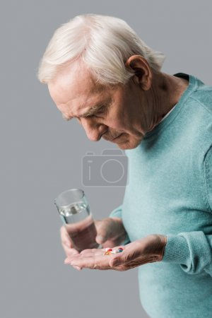 Photo for Upset retired man looking at pills while holding glass of water isolated on grey - Royalty Free Image