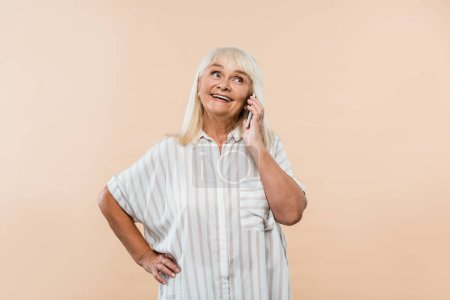 Photo for Cheerful retired woman standing with hand on hip and talking on smartphone isolated on beige - Royalty Free Image