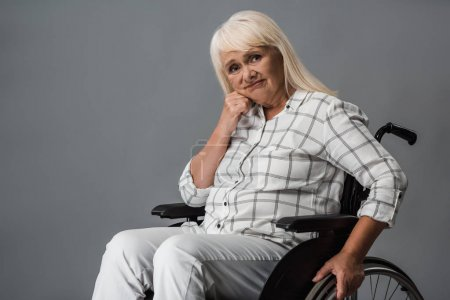 Photo for Upset and disabled retired woman sitting in wheelchair and looking at camera on grey - Royalty Free Image
