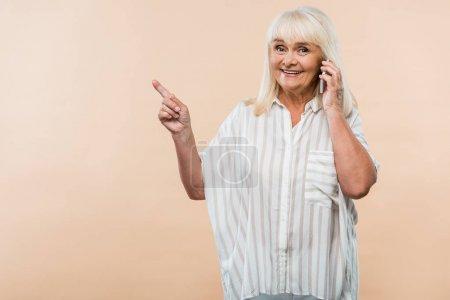 Photo pour Joyeuse femme retraitée pointant du doigt tout en parlant sur smartphone isolé sur beige - image libre de droit