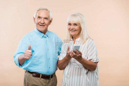 Photo for Cheerful retired woman holding smartphone near husband showing thumb up isolated on beige - Royalty Free Image