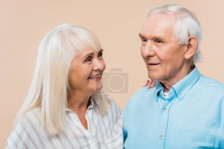 Photo for Happy retired woman looking at man with grey hair isolated on beige - Royalty Free Image