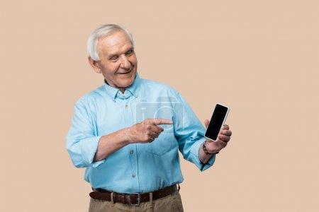 Foto de Hombre jubilado feliz con el pelo gris apuntando con el dedo en el teléfono inteligente con la pantalla en blanco aislada en beige - Imagen libre de derechos
