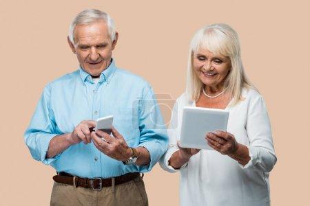 heureux homme à la retraite en utilisant smartphone près de la femme avec tablette numérique isolé sur beige