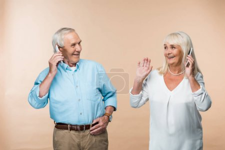 Photo for Happy retired couple with grey hair using smartphones isolated on beige - Royalty Free Image