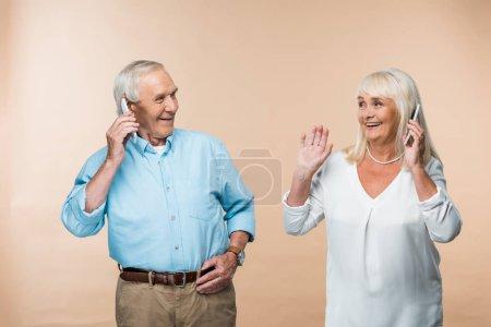 Photo pour Heureux couple retraité avec les cheveux gris en utilisant des smartphones isolés sur beige - image libre de droit