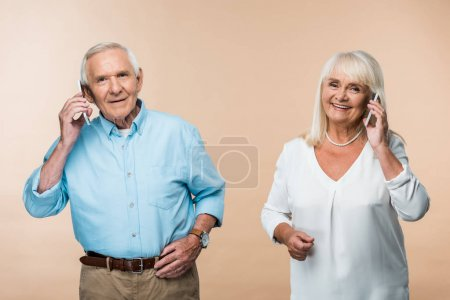 Photo for Happy retired couple with grey hair talking on smartphones isolated on beige - Royalty Free Image
