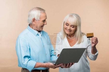 Photo pour Femme retraitée gaie retenant la carte de crédit près du mari aîné avec l'ordinateur portatif d'isolement sur le beige - image libre de droit