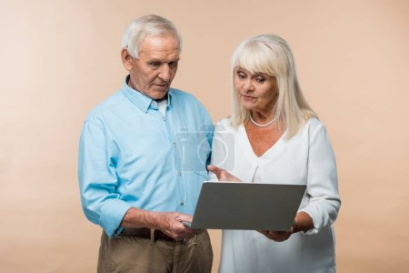 Photo for Retired woman gesturing while looking at laptop near senior husband isolated on beige - Royalty Free Image