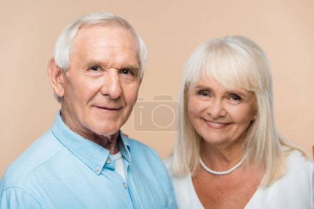 Photo for Selective focus of senior man smiling near retired wife isolated on beige - Royalty Free Image