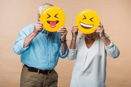 Foto de Kiev, Ucrania - 14 de junio de 2019: pareja jubilada cubriendo rostros con emoticonos felices amarillos aislados en beige - Imagen libre de derechos