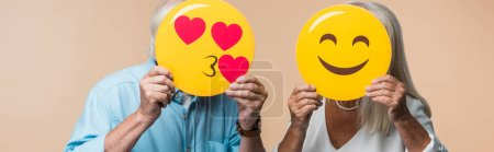 KYIV, UKRAINE - JUNE 14, 2019: panoramic shot of senior couple covering faces with yellow happy smileys isolated on beige
