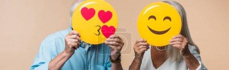 Foto de KYIV, UKRAINE - JUNE 14, 2019: panoramic shot of senior couple covering faces with yellow happy smileys isolated on beige - Imagen libre de derechos