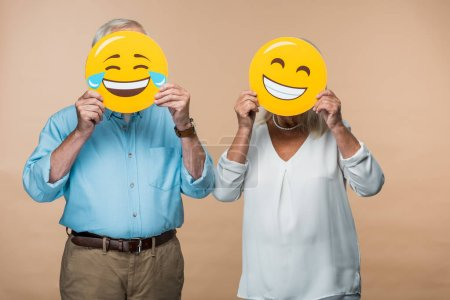 Photo for KYIV, UKRAINE - JUNE 14, 2019: senior couple covering faces with yellow happy smileys isolated on beige - Royalty Free Image