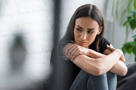 Photo pour Foyer sélectif de pleurer jeune femme souffrant de dépression tout en étant assis avec les bras croisés et en regardant loin - image libre de droit