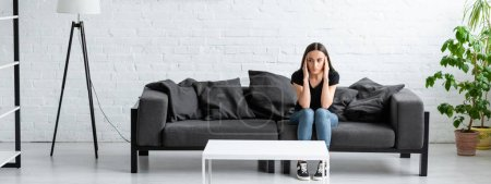 Photo for Depressed young woman sitting on sofa in spacious room and holding hands near head - Royalty Free Image
