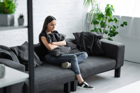 Photo for Depressed young woman sitting on sofa at home and hugging pillow - Royalty Free Image