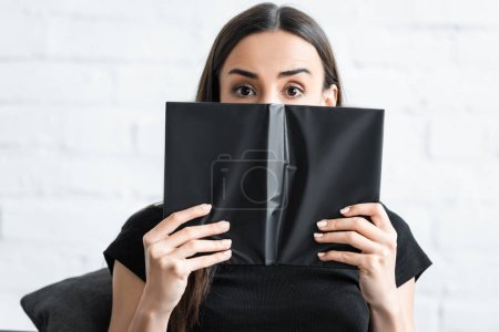 Photo for Scared young woman suffering from dementia covering face with notebook and looking at camera - Royalty Free Image