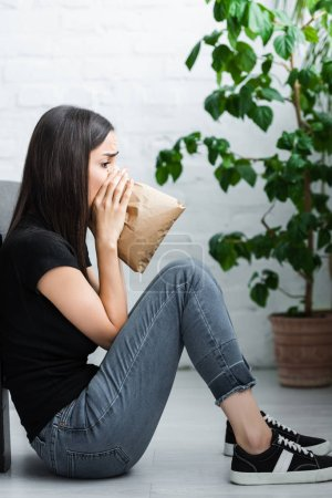 Photo for Side view of young woman sitting on floor and breathing into paper bag while suffering from panic attack - Royalty Free Image