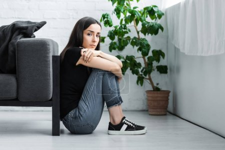 Photo for Depressed young woman sitting on floor at home and looking at camera - Royalty Free Image