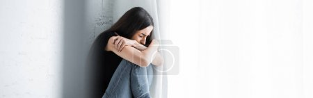 Photo for Panoramic shot of depressed young woman crying while sitting by window and hiding face in crossed arms - Royalty Free Image