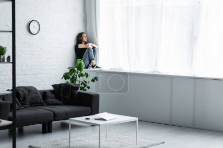 Photo for Depressed young woman sitting on window sill at home and looking away - Royalty Free Image