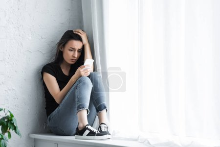 Photo for Depressed young woman sitting on window sill at home and using smartphone - Royalty Free Image