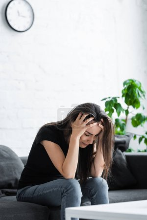 Photo for Depressed girl crying while sitting on couch at home and holding hands on head - Royalty Free Image