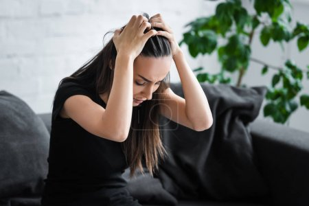 Photo for Frustrated young woman suffering from depression while sitting on couch and holding hands on head - Royalty Free Image